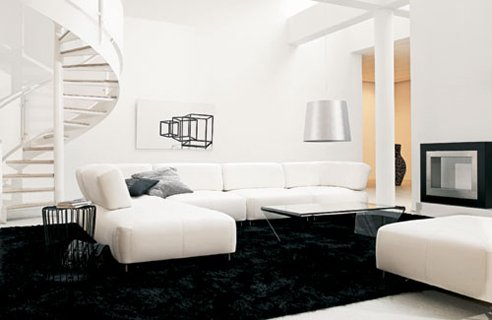 White-engrained-living-room-with-curved-staircase-black-carpet-coffee-table-and-white-sofa-set